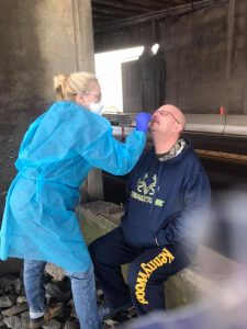 Female doctor swabbing man's nose for COVID-19 test under a bridge.