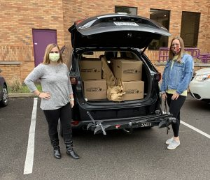 Two woman at back of car with boxes of food loaded in back