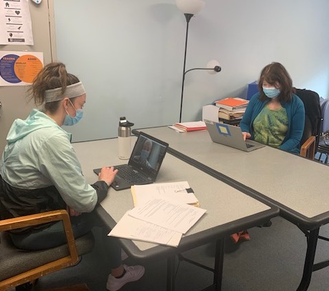 Two women conducting telehealth visits via computer.