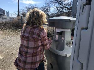 Woman washing hands at sanitation station (sink).