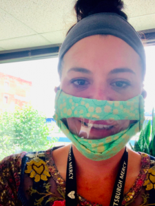 Woman wearing face covering with clear insert at the mouth area