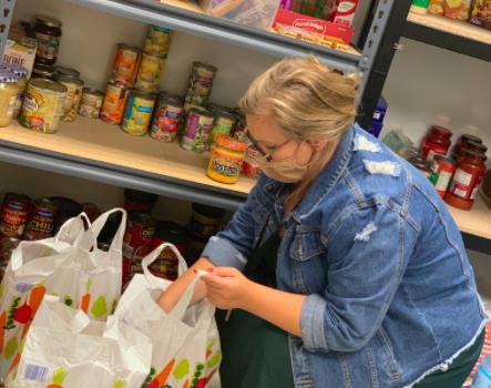 Woman sorting groceries at food pantry