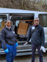Woman and man with boxes of food loaded into van.
