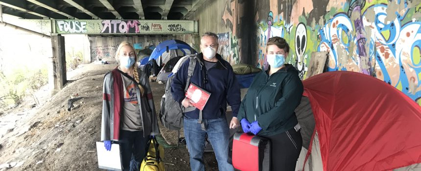 Three people under bridge with medical equipment.