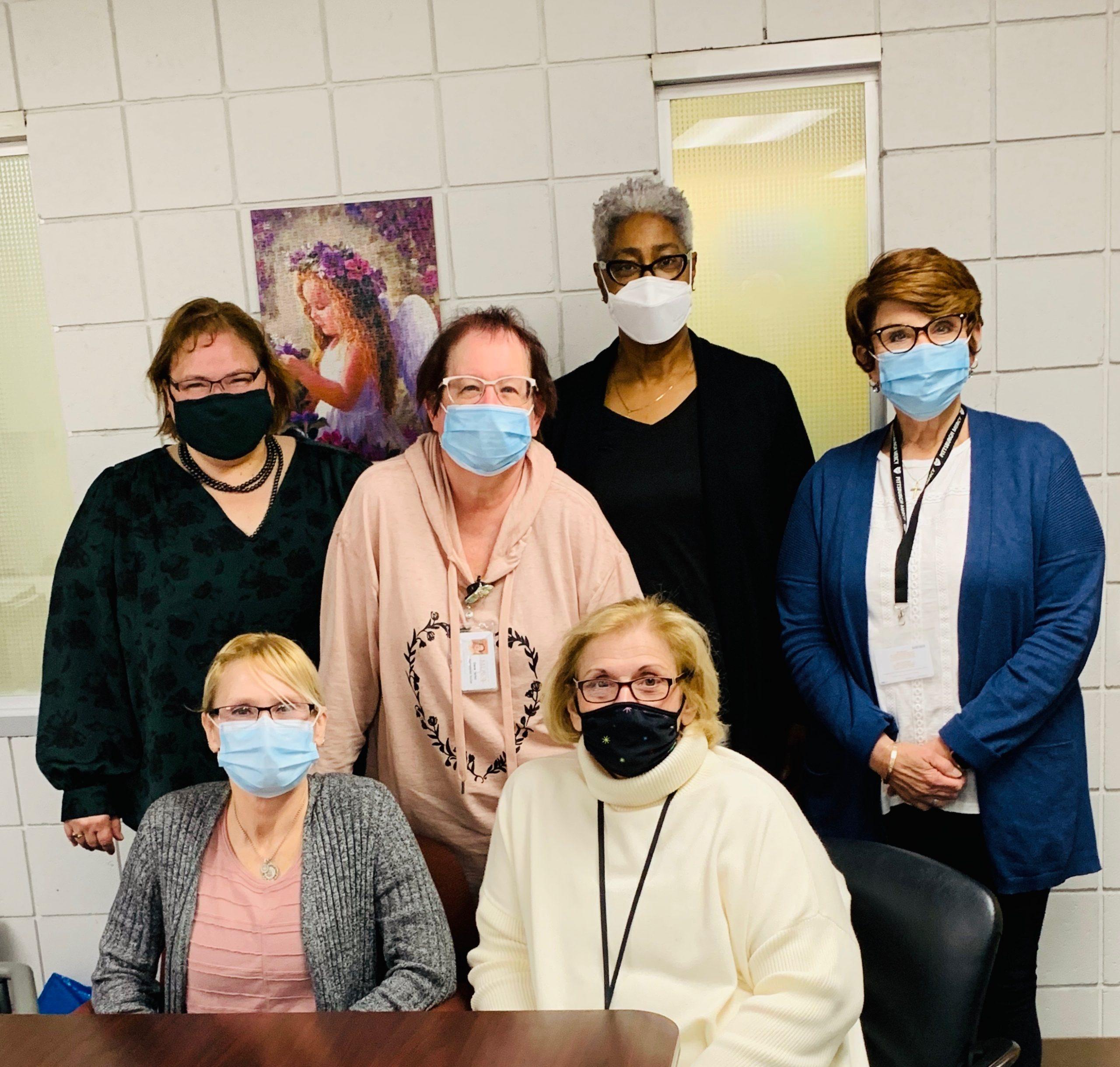 Six women posed, wearing COVID-19 face masks