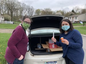 Two women with medical supplies in trunk of car