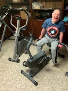 Smiling man on recumbent exercise bike.