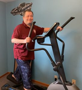 Smiling man on elliptical exercise equipment.