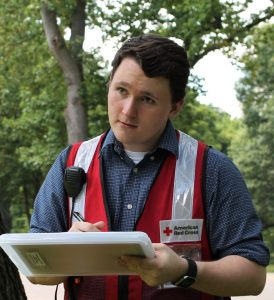 Man in Red Cross vest with clipboard