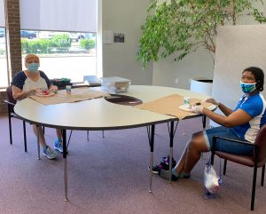 Two women seated at table working on craft projects