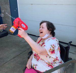 Woman using bubble gun to blow bubbles.