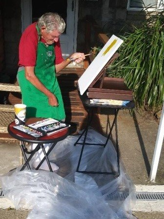 Man painting canvas on easel.