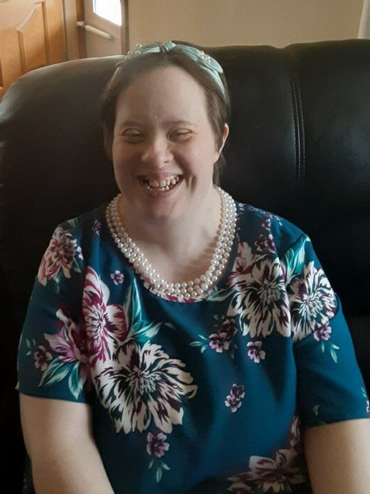 Smiling woman dressed up with pearls seated in a chair.